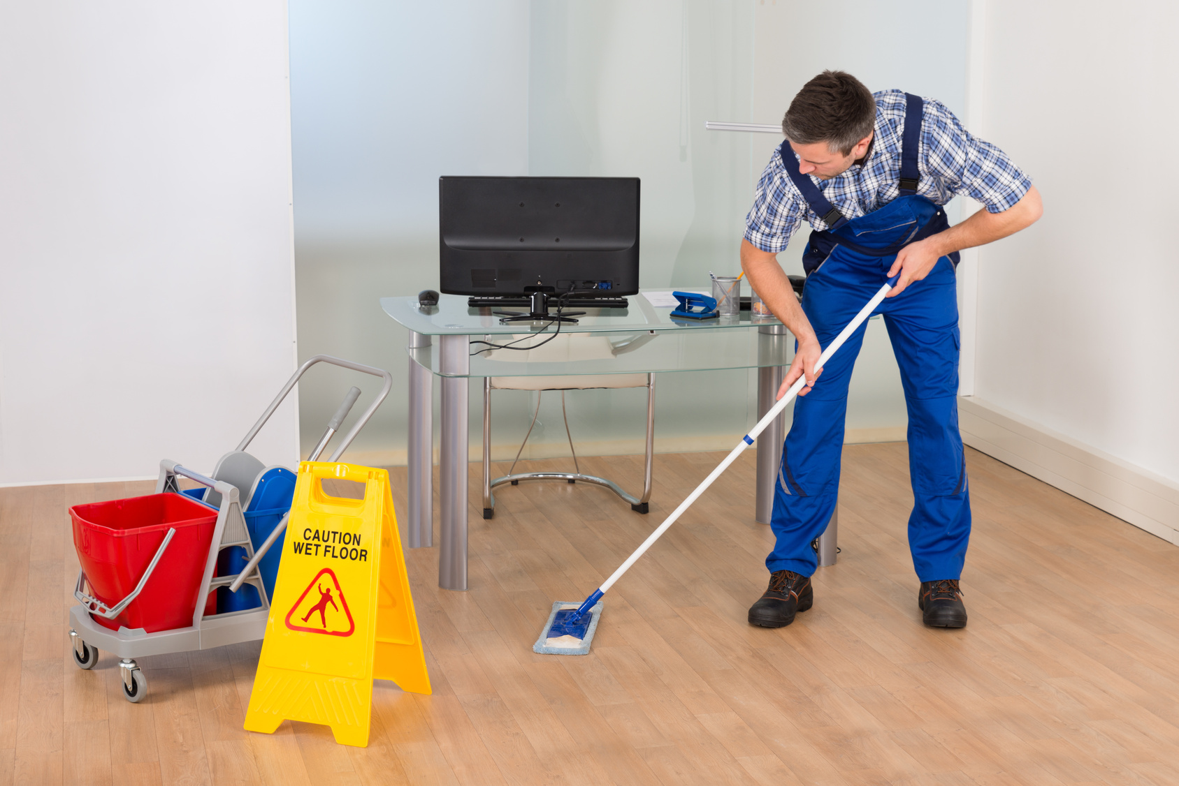 Man Mopping Office With Wet Floor Sign